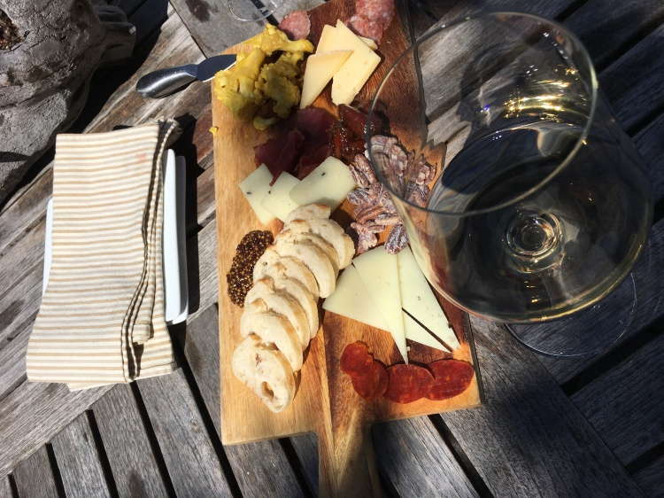 A meat and cheese charcuterie board with glass of white wine at folktale winery and vineyards