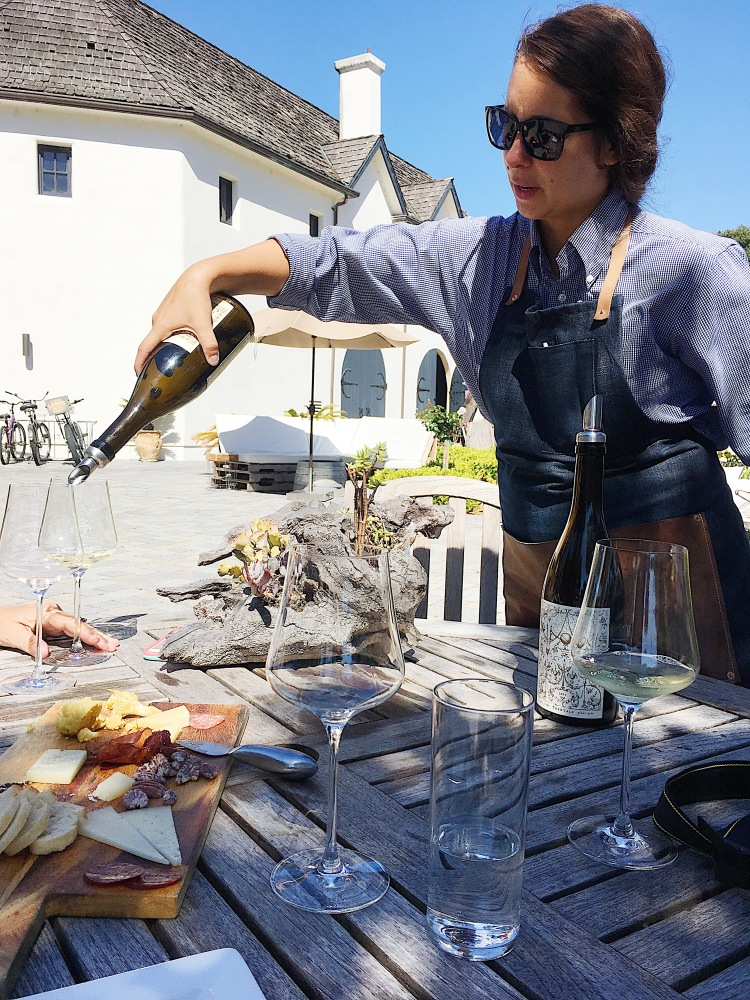A wine server pours a glass of white wine at folktale winery and vineyards