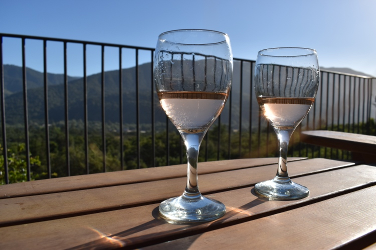 Two glasses of rosé sit atop a table on the deck of a guesthouse in carmel valley