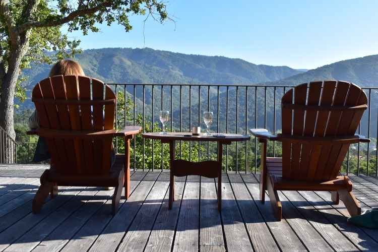 A woman relaxes in an adirondack chair on the deck of a guesthouse in Carmel Valley overlooking incredible mountain views