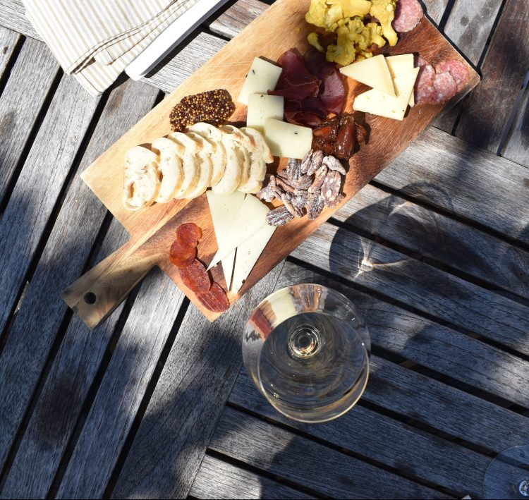 a charcuterie plate with white wine at folktale winery in carmel california