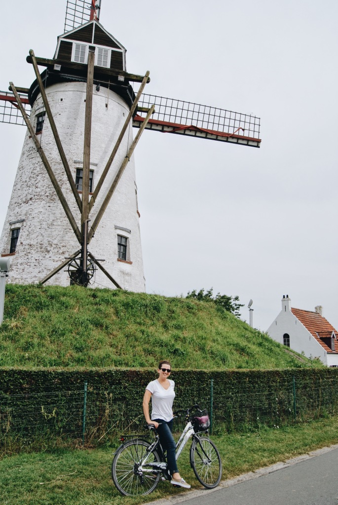 Erin from cathedrals and cafes biking through The Netherlands by a large white windmill