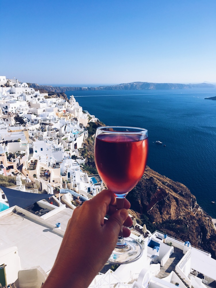 A glass of rosé wine against the backdrop of Santorini, Greece and the caldera
