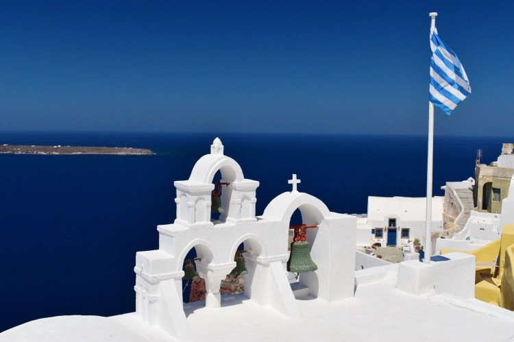 A set of chapel bells with Greek flag in Santorini, Greece