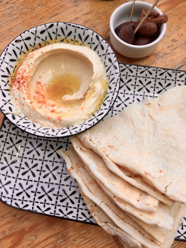 A plate of hummus, olives, and pita bread in Athens, Greece