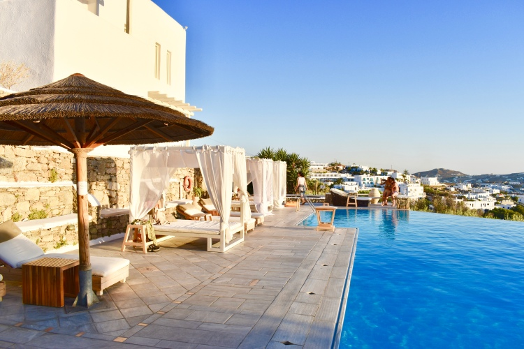 Lounge beds by infinity pool at Vencia Boutique Hotel Mykonos