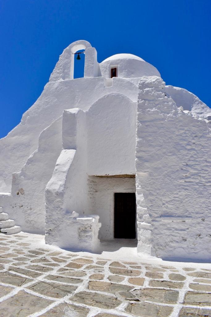 White chapel in Mykonos against a deep blue sky