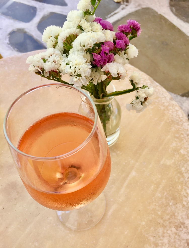 A glass of rosé next to a vase of purple and white flowers in Little Venice, Mykonos Greece