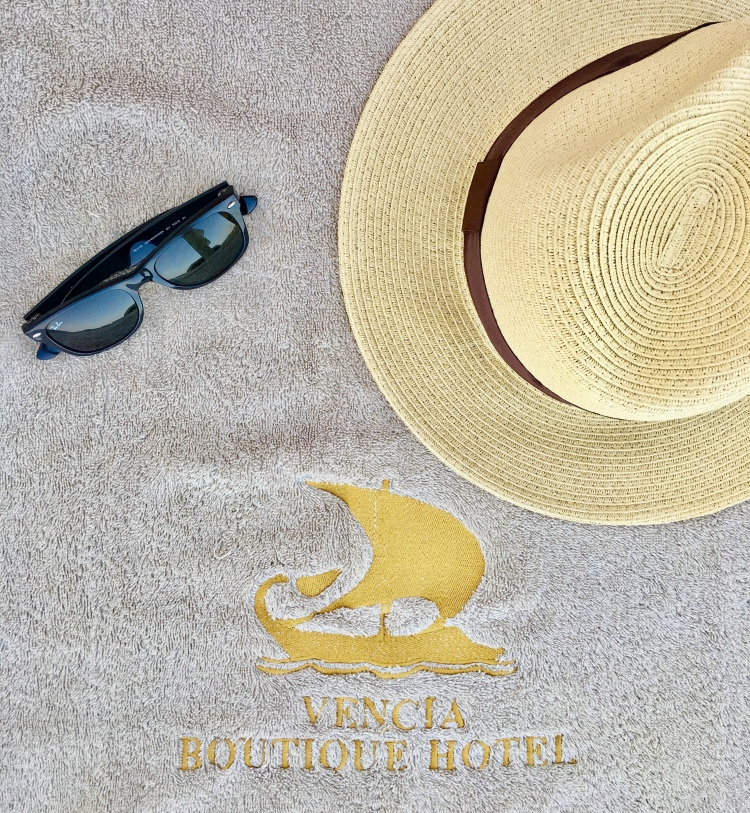 Pool towel from Vencia Boutique Hotel with Rayban sunglasses and Panama hat in Mykonos Greece
