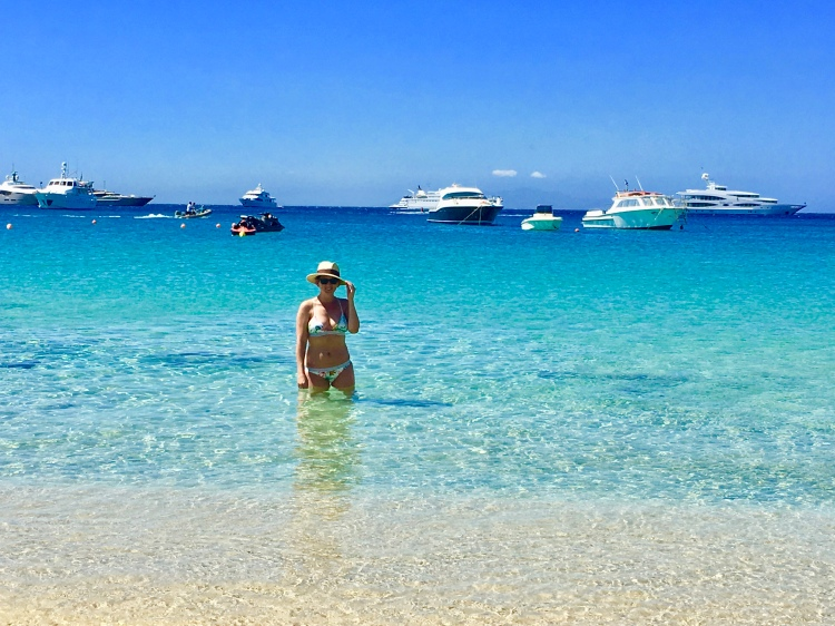 Erin from Cathedrals and Cafes Blog stands in the water at Platis Yialos Beach in Mykonos, Greece wearing a palm print bikini from H&M
