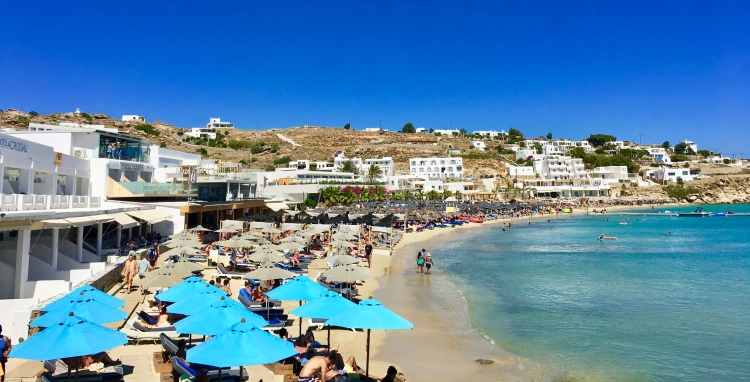 The shoreline of Platis Yialos Beach dotted with turquoise umbrellas in Mykonos, Greece