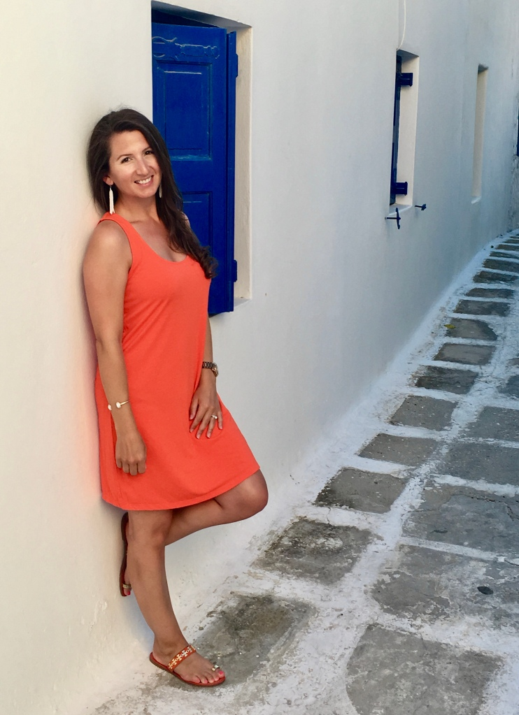Erin from Cathedrals and Cafes Blog wearing an orange shift dress posing in an alley next to a blue shutter in Mykonos