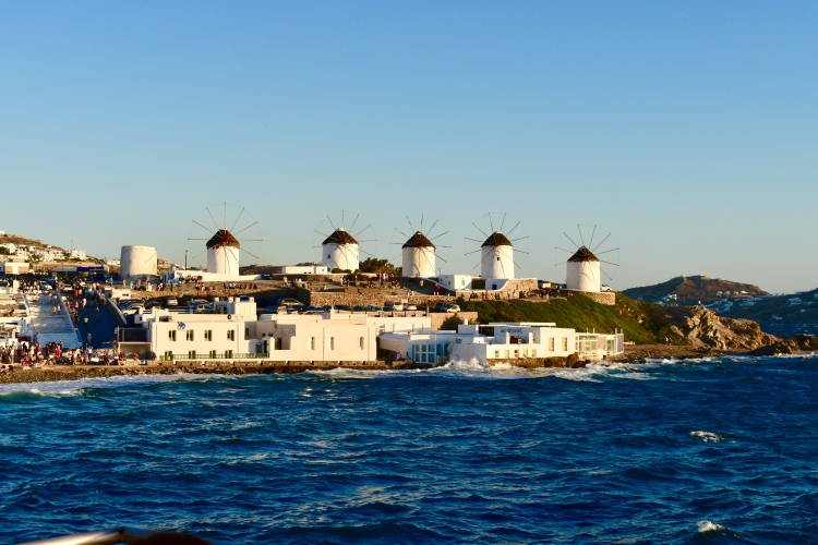 Five windmills on Mykonos island, Greece stand facing the sea at sunset