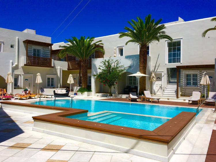 View of Nissaki Beach Hotel Pool with large palm trees, Naxos Greece