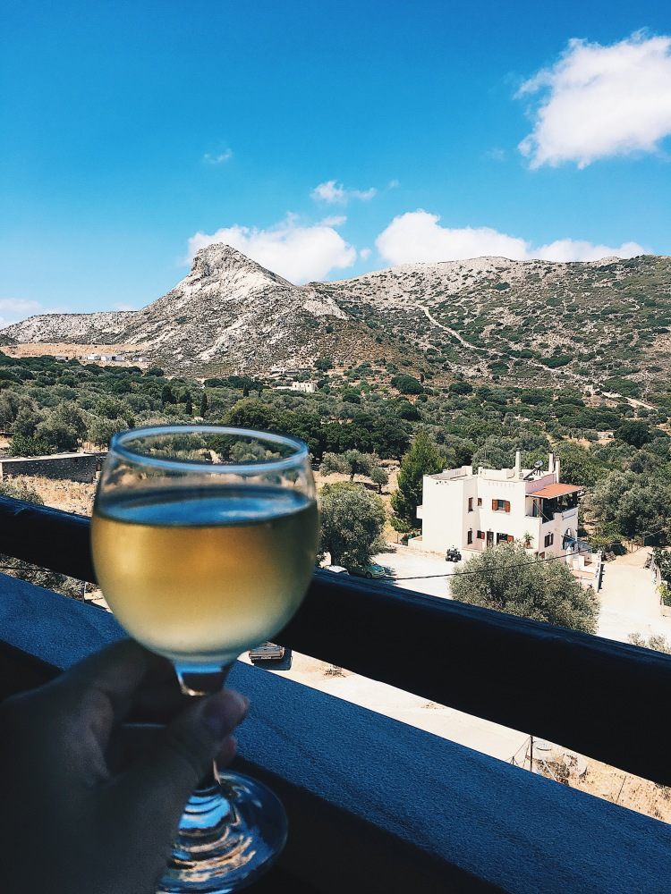 A glass of Moscato white wine with mountains in the background in Filoti, Naxos Greece