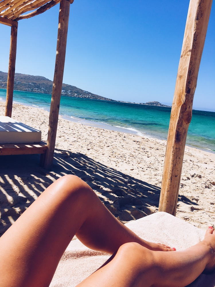 Erin from Cathedrals and Cafes lounges on a sunbed on Plaka Beach in Naxos, Greece