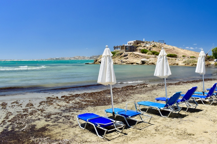 Blue lounge chairs and white umbrellas on Nissaki Beach in Naxos, Greece