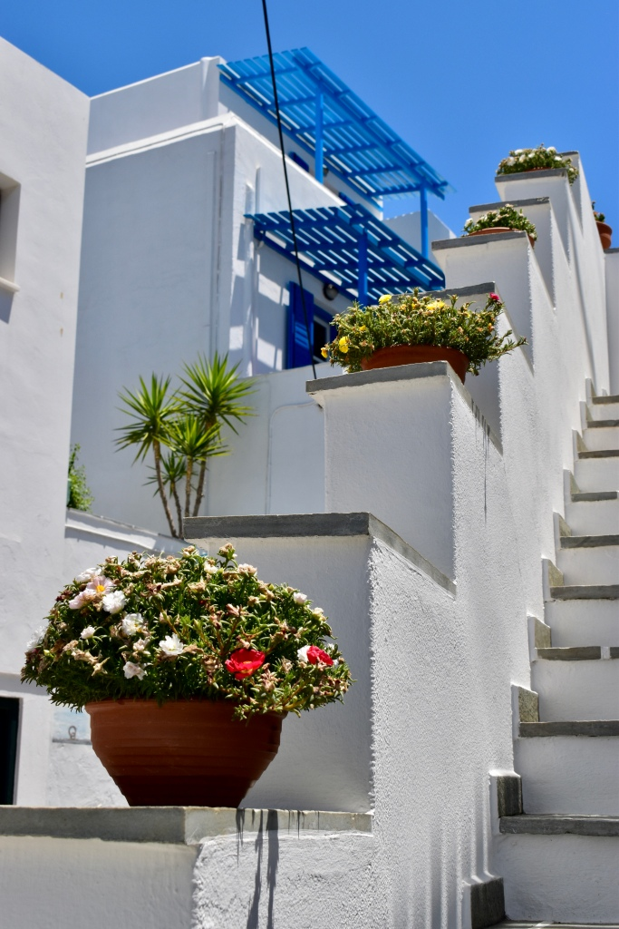 A white staircase with colorful potted flowers in Naxos, Greece