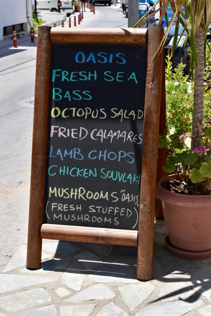 A chalkboard menu outside of Oasis Restaurant in Naxos Greece