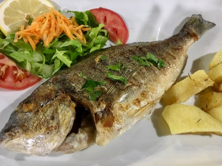 A grilled seabream fish with salad and potatoes from Oasis Restaurant in Naxos, Greece
