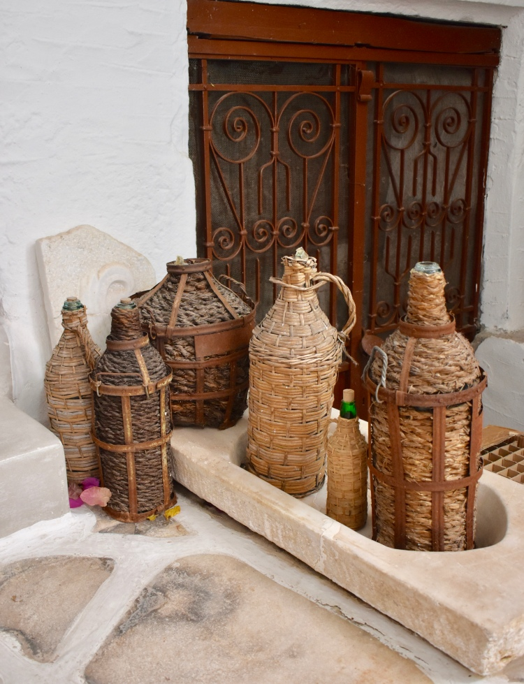 A collection of wicker covered glass bottles at Kitron distillery in Halki, Naxos Greece