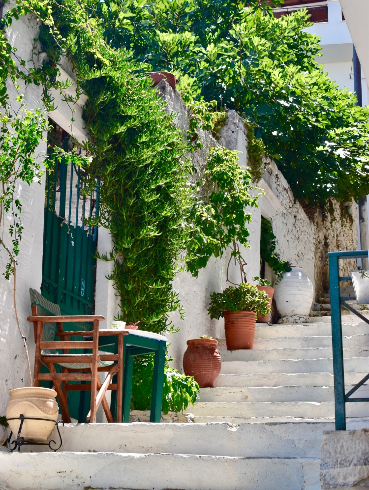 A stairway with clay pots, ivy, and green doors in Filoti, Naxos Greece