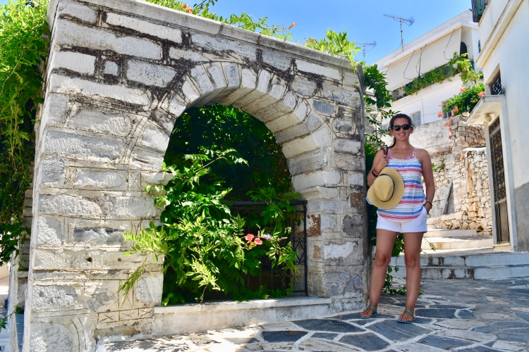 Erin from Cathedrals and Cafes posing with a stone arch in Filoti, Naxos Greece