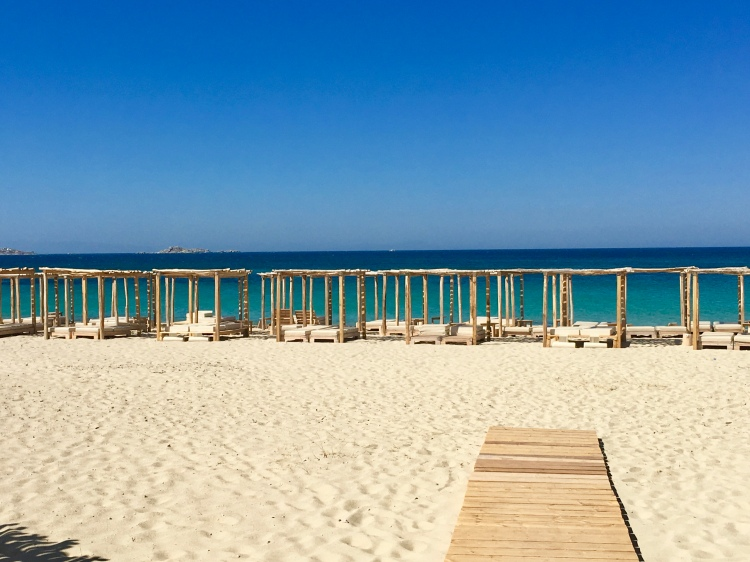 A row of sunbeds and a wooden boardwalk facing the sea on Plaka Beach in Naxos, Greece