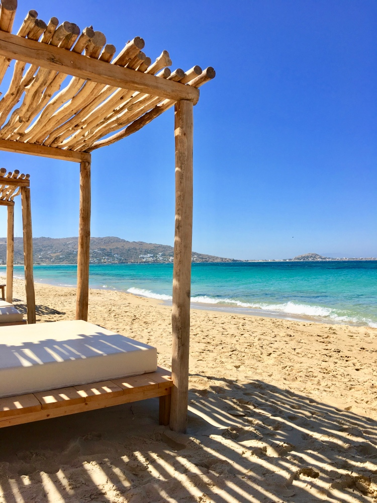 A wooden sunbed with awning stands on Plaka Beach facing the crystal clear blue waters in Naxos, Greece