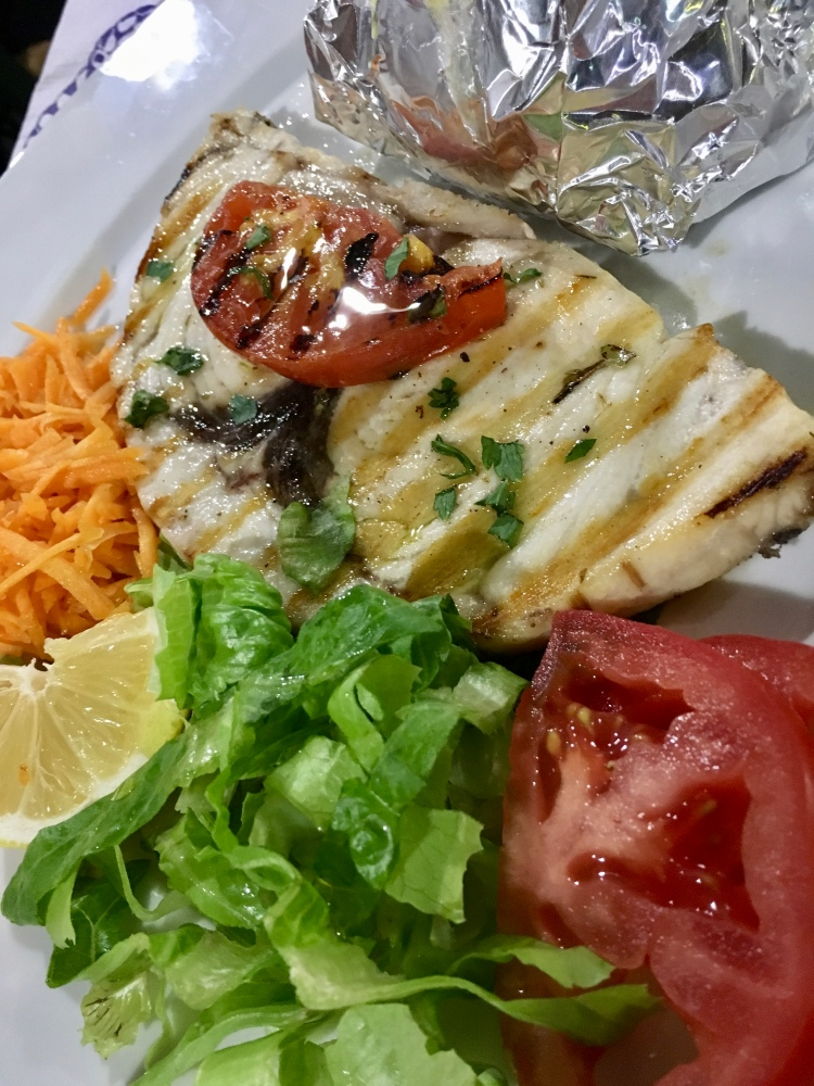 A plate of grilled swordfish with green salad from Oasis Restaurant in Naxos, Greece