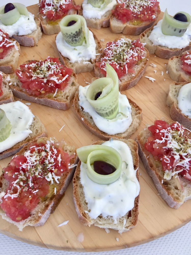 A plate of bruschetta with tzatziki, tomatoes, and olives aboard the catamaran Danae with Naxos Yachting