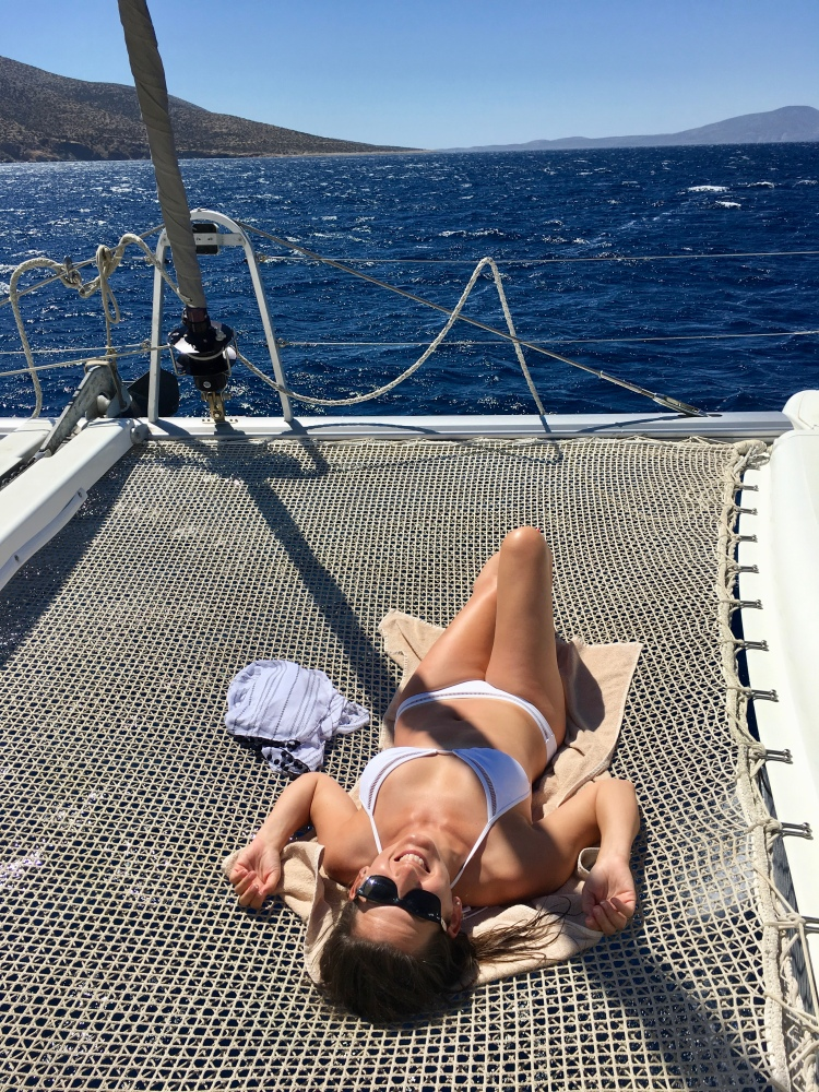 Erin from Cathedrals and Cafes on catamaran Danae's net trampoline with Naxos Yachting in Naxos, Greece
