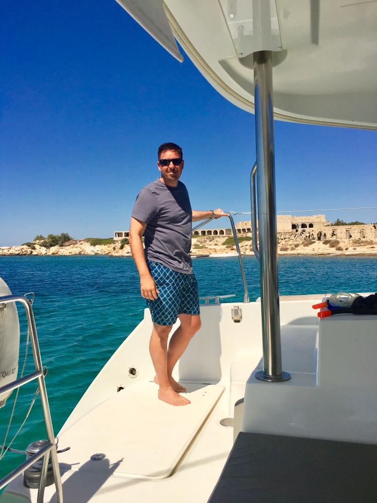 Erin's husband on the catamaran Danae at abandoned resort hotel in Naxos, Greece