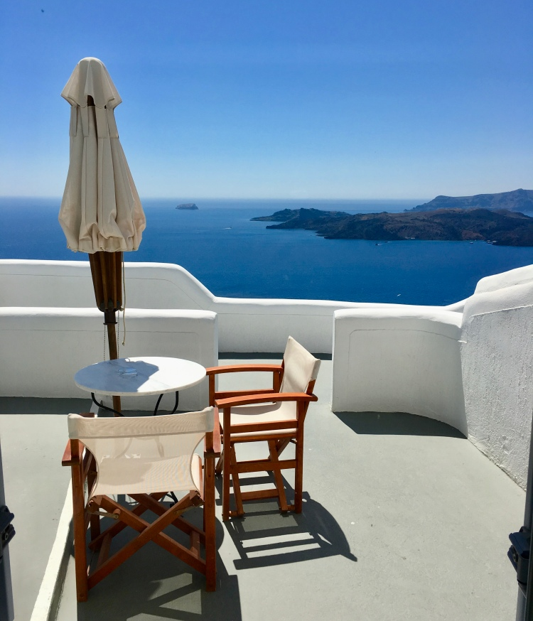 The private terrace with umbrella and patio set of a hotel room at Volcano View Hotel in Santorini Greece