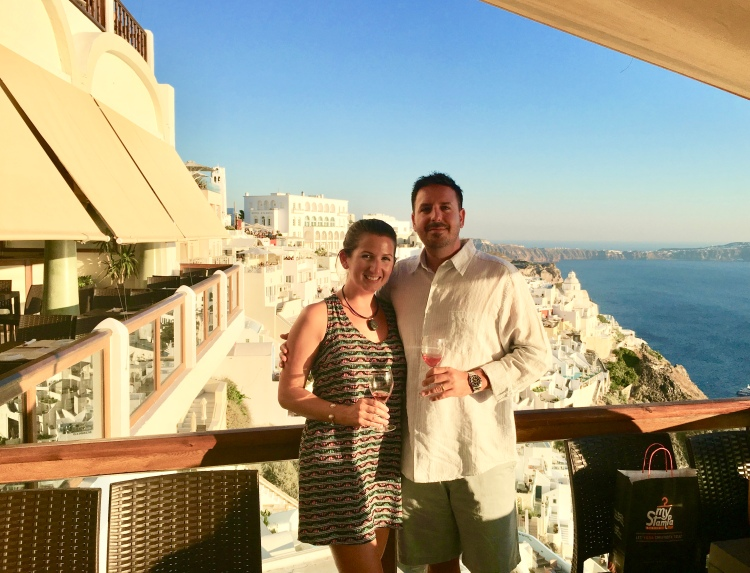 Erin from Cathedrals and Cafes blog with her husband having wine at Select Cafe in Santorini Greece