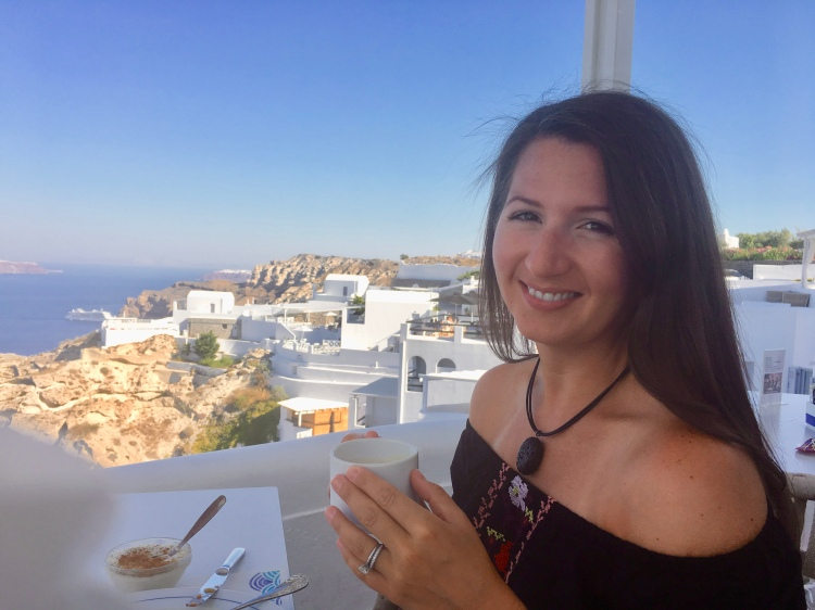 Erin from Cathedrals and Cafes blog sips on coffee at the breakfast table at Volcano View Hotel in Santorini Greece