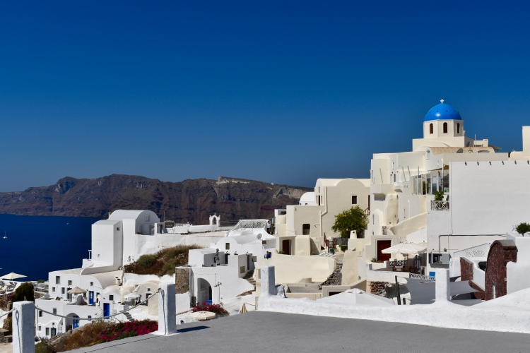 A view of a blue dome and white washed buildings in Santorini Greece