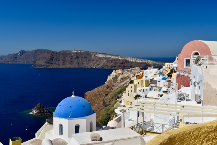 A white washed building with blue dome sits high above the sea in Santorini