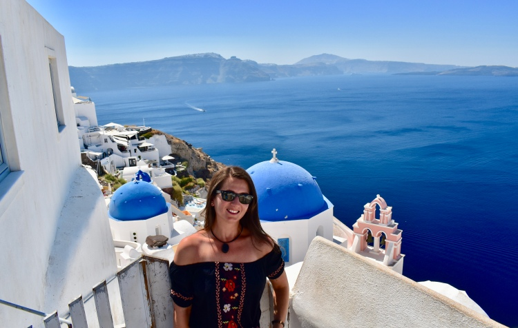 Erin from Cathedrals and Cafes blog poses next to a blue domed building in Oia Santorini Greece