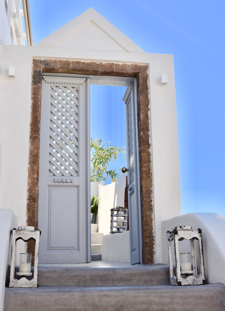 A blue wooden door stands open and is flanked by two lanterns in Santorini Greece
