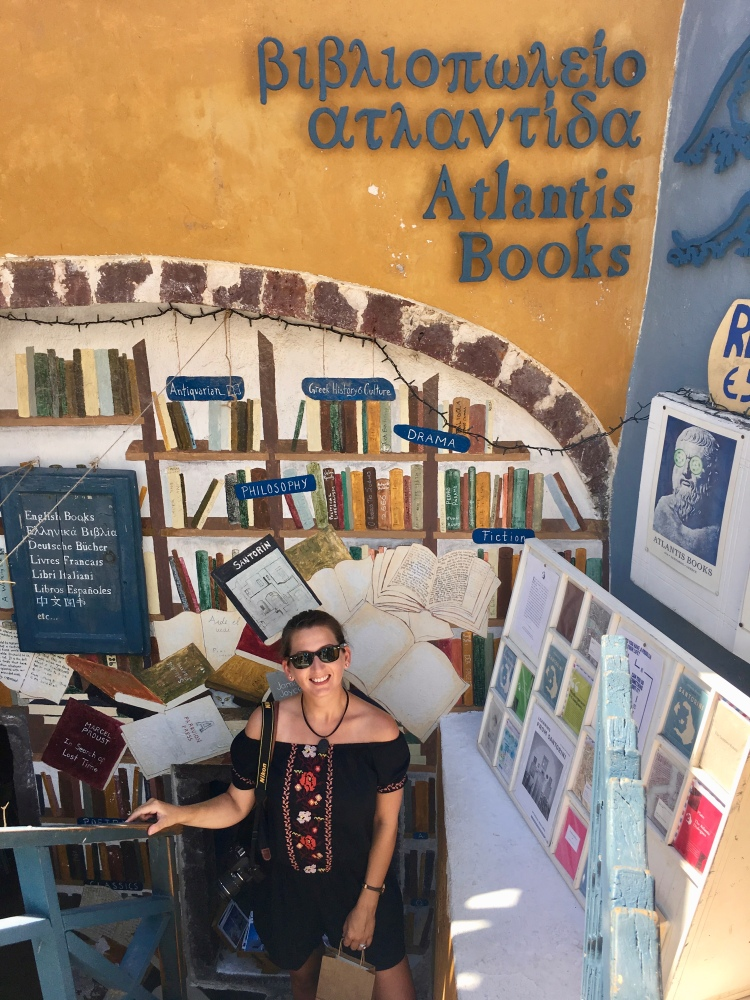 Erin from Cathedrals and Cafes blog at the entrance to Atlantis Books in Oia Santorini Greece