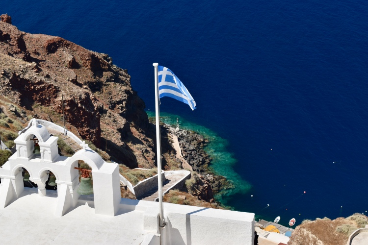 A Greek flag flies in the wind above church bells and the sea in Oia Santorini Greece