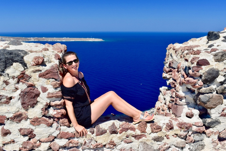 Erin from Cathedrals and Cafes blog sits in a stone alcove high above Ammoudi Bay in Oia, Santorini Greece
