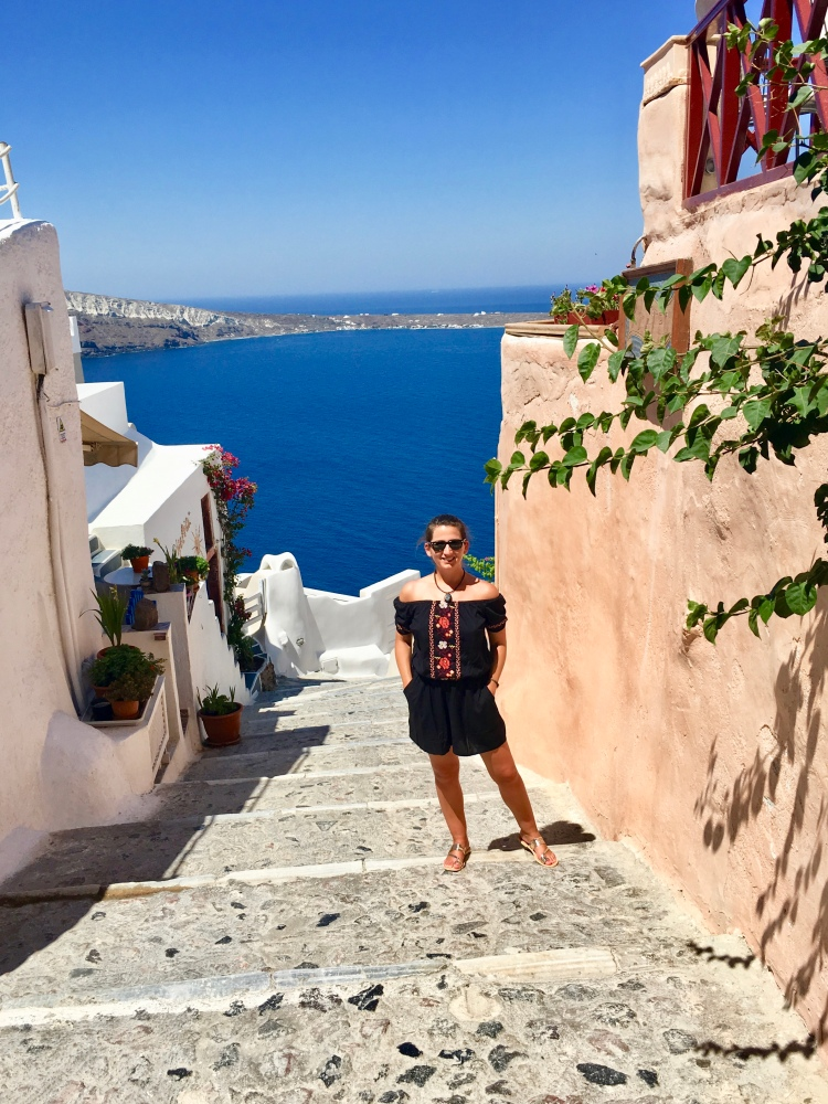 Erin from Cathedrals and Cafes blog poses on a large stone stairway that leads to Ammoudi Bay in Oia, Santorini Greece