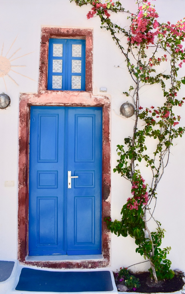 A blue door with floral ivy in Oia Santorini Greece