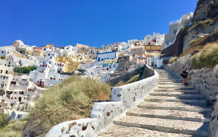 Erin from Cathedrals and Cafes blog navigates a long stone stairway to Ammoudi Bay in Oia Santorini Greece