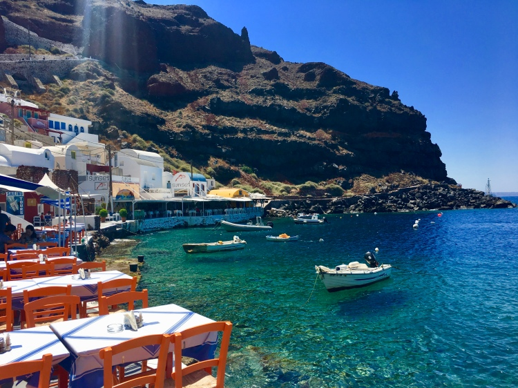 Boats along the shore of Ammoudi Bay float next to cafe chairs in Oia Santorini Greece