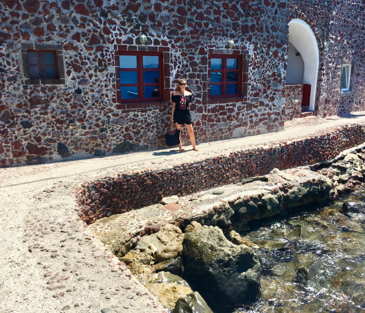 Erin from Cathedrals and Cafes blog stands along the shore in front of a red stone building in Ammoudi Bay, Oia Santorini Greece