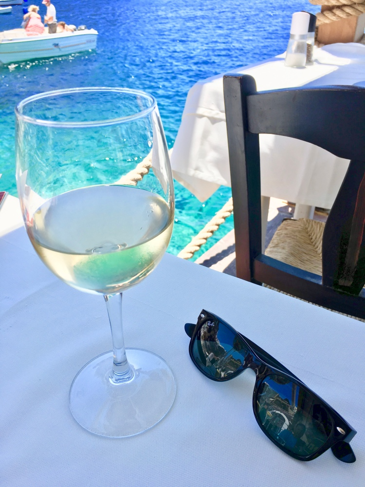 A glass of white wine and rayban sunglasses on a cafe table in Ammoudi Bay, Oia Santorini Greece
