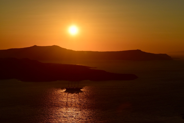 A bright orange sun sets over the caldera of Santorini Greece while a sailboat sails by